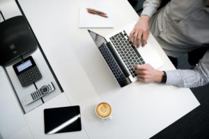 Corporate man works at desk with laptop and coffee