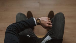 Man in suit looks at watch
