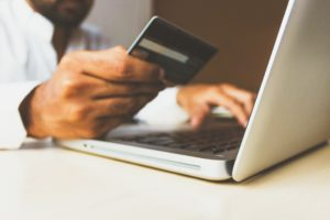 Man uses credit card to pay online laptop