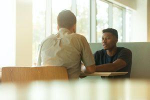 Seeking help, talking to a friend in a light open space